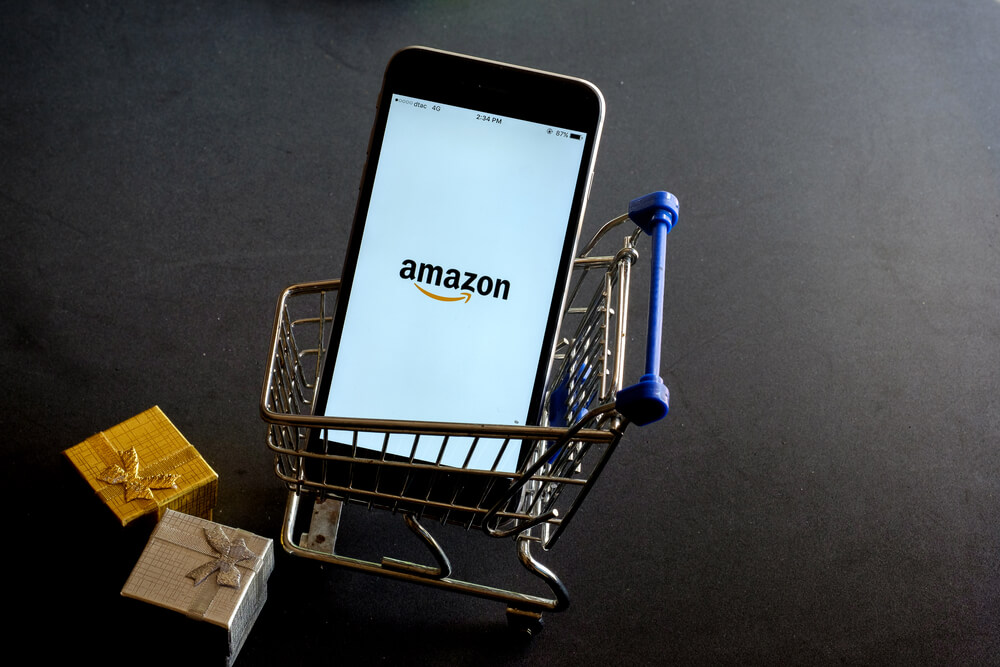 An Amazon app is used on a smartphone that is placed in a shopping cart